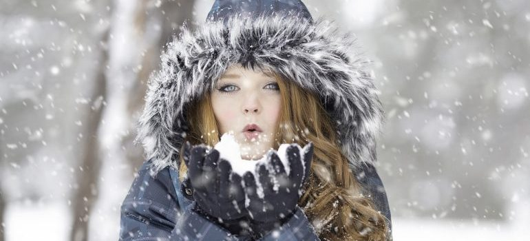 A girl blowing snow out of her hands.