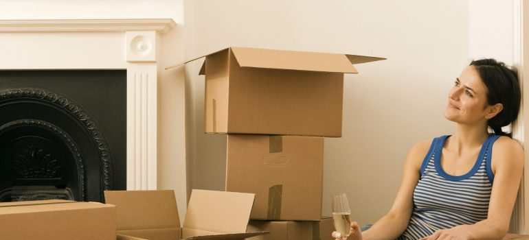 a girl sitting next to a pile of moving boxes