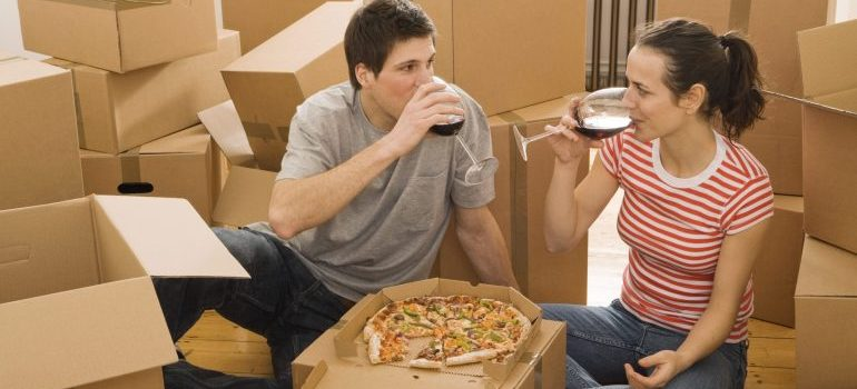 Couple having wine and pizza in new home
